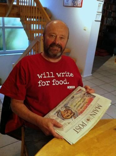 Anton Sahlender daheim im Foodblogger-Shirt und Main-Post in der Hand.
